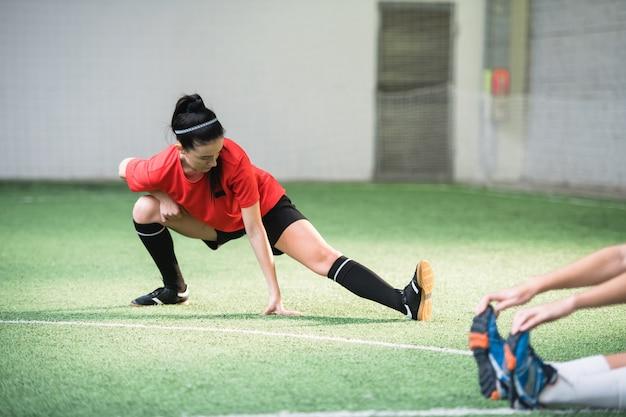 Actief meisje in sportuniform doen oefening voor het strekken van benen op voetbalveld tijdens het trainen voor de wedstrijd