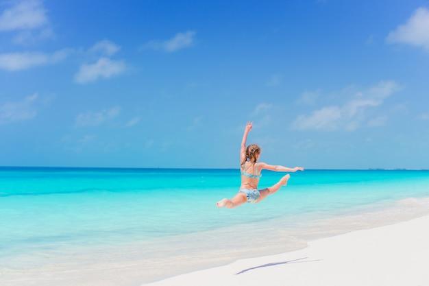 Actief meisje op het strand met veel plezier aan de kust en een sprong te maken