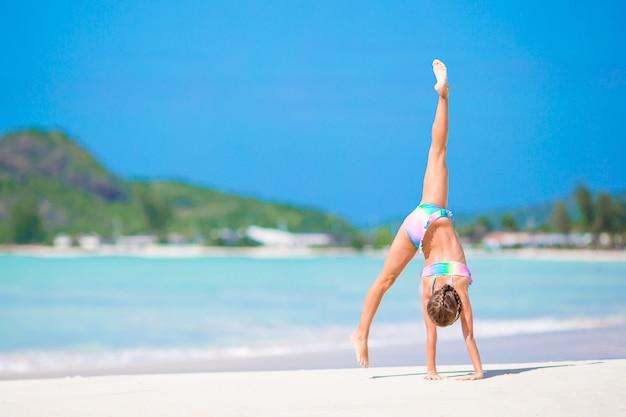 Actief meisje op het strand met veel plezier. leuk jong geitje dat sportieve oefeningen op de kust maakt