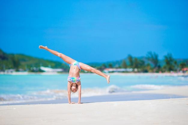 Actief meisje op het strand met veel plezier. schattige jongen sportieve oefeningen maken aan de kust