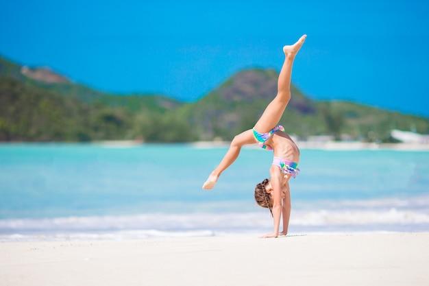 Actief meisje op het strand met veel plezier. sportief jong geitje dat het wiel op de kust maakt