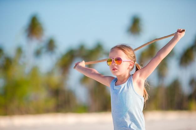 Actief meisje op wit strand dat pret heeft. closeup kind achtergrond de zee
