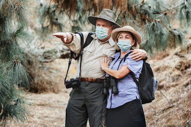 Actief senior koppel genietend van de schoonheid van de natuur tijdens covid-19 pandemie