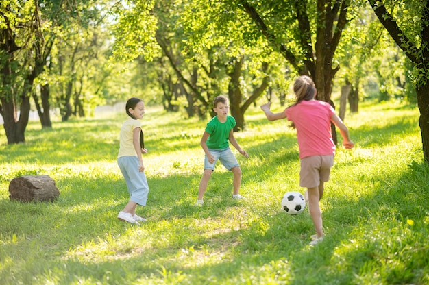 Actief spelen. drie jonge energieke kinderen speelden op een zonnige dag voetbal op groen gazon