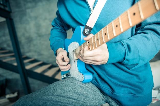 Actief spelen. professionele muzikant in fel sweatshirt met blauwe elektronische gitaar terwijl hij alleen thuis is
