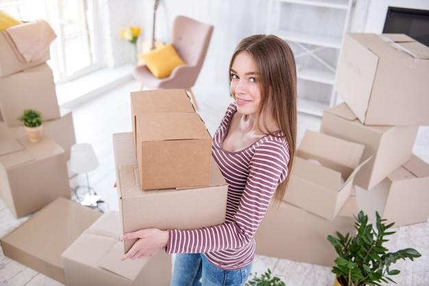 Actief uitpakken. charmante jonge vrouw die twee dozen vasthoudt en naar de camera glimlacht alvorens ze verder te openen