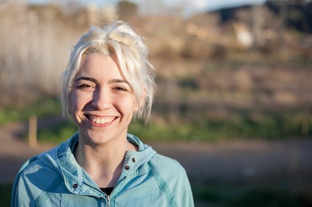 Actief vrolijk blonde die na een looppas in een park op een zonnige dag pauzeren