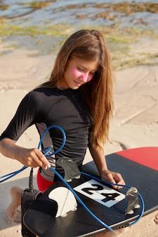 Actief zomerrustconcept. buiten schot van aantrekkelijke jonge vrouw in badpak, fixeert riem op surfplank, klaar om te vechten tegen stroom