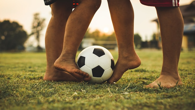Actiesport buitenshuis van een groep kinderen die plezier hebben in het voetballen