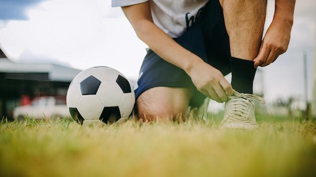 Actiesport in openlucht van de voetballer die van de voetbalbal voor oefening speelt