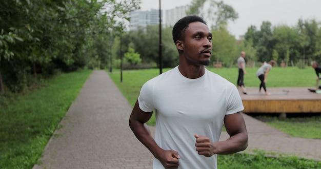Actieve afro-amerikaanse man runner training alleen, rennen in leeg stadspark. ochtend training. concept van gezonde levensstijl.