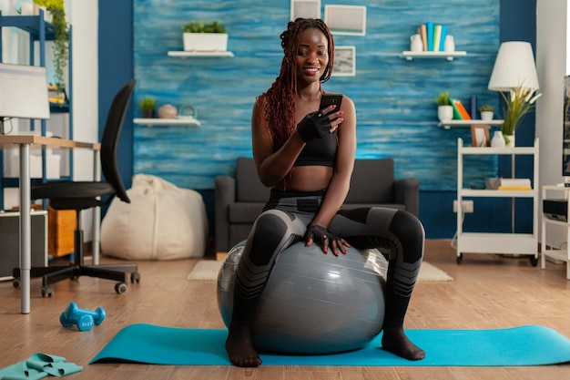 Actieve atletische zwarte vrouw chatten op smartphone zittend op zwitserse bal in huis woonkamer na w...
