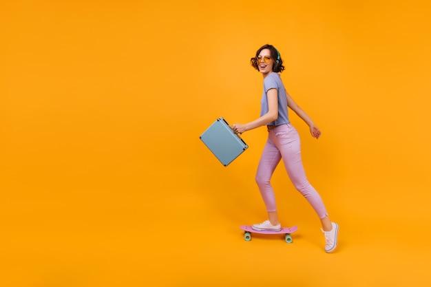 Actieve blanke vrouw met valise schaatsen. binnen schot van prachtig krullend meisje dat zich op longboard bevindt.