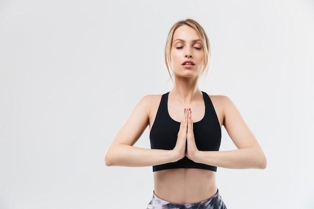 Actieve blonde vrouw gekleed in sportkleding uit te werken en te mediteren met handpalmen samen geïsoleerd over witte muur