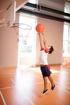 Actieve donkerharige schooljongen die sportkleding draagt en de bal in de mand gooit