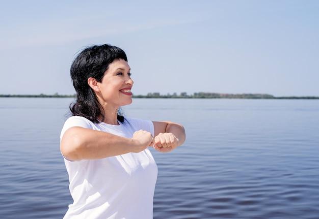 Actieve en gelukkige senior vrouw te oefenen in de buurt van de rivier