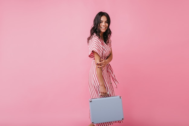 Actieve en positieve brunette gaat met handbagage naar de luchthaven. portret van gelooid meisje in gestreepte sundress.