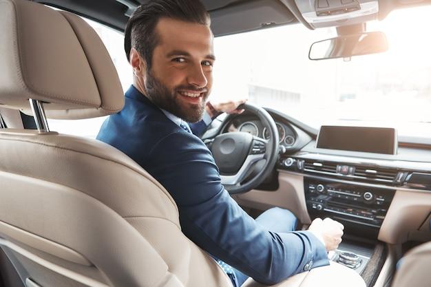 Actieve en succesvolle gelukkige bebaarde zakenman in formele kleding die naar de camera kijkt en glimlacht terwijl