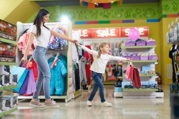 Actieve familie die papieren zakken houdt en in de winkel loopt