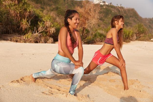Actieve fitnessvrouwen doen lunges op het strand, strekken hun benen voordat ze rennen, poseren in de richting van de zee op het zandstrand