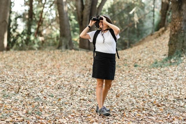 Actieve gepensioneerde vrouw die een verrekijker gebruikt om de schoonheid van de natuur te zien