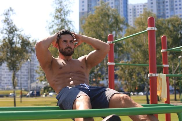 Actieve gespierde atleet doet buikspieren trainen en crunches buiten, trainen.