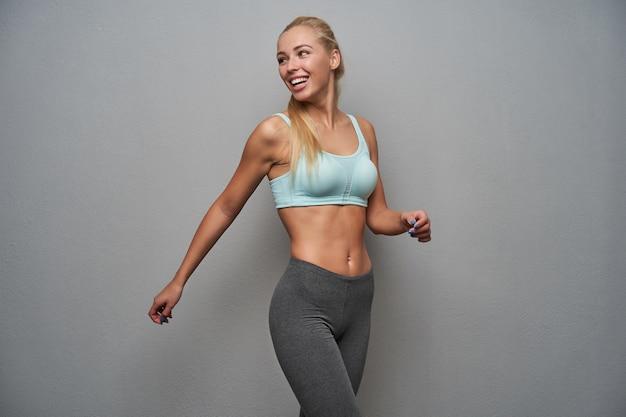 Actieve gezonde jonge vrouw met lang blond haar die vrolijk over haar schouder kijkt en vreugdevol glimlacht, mint top en grijze legging draagt terwijl ze zich voordeed op de lichtgrijze achtergrond