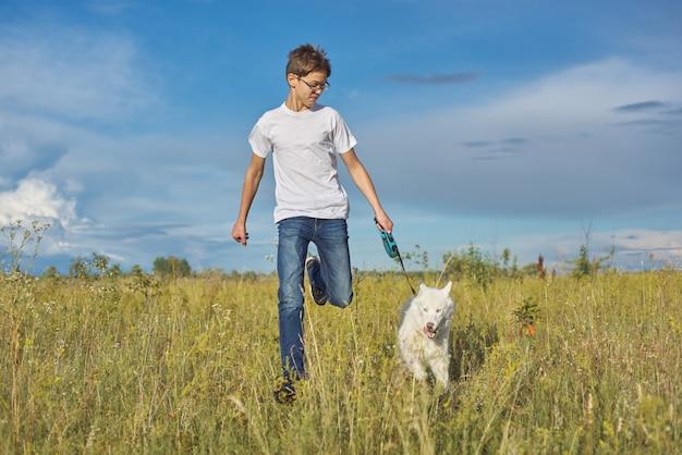 Actieve gezonde levensstijl, tienerjongen die met witte schor hond loopt