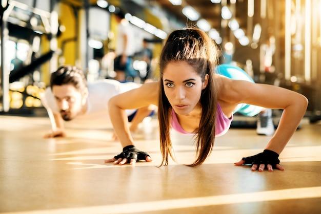 Actieve gezonde mooie vrouw doet push-ups met handschoenen in de buurt van trainer in de zonnige sportschool.