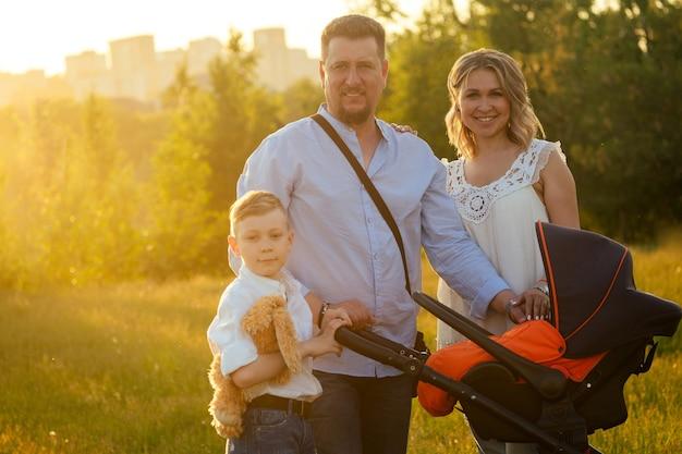 Actieve grote gelukkige familie vader, moeder, zoon en baby in kinderwagen wandelen in het park in de zonsondergang