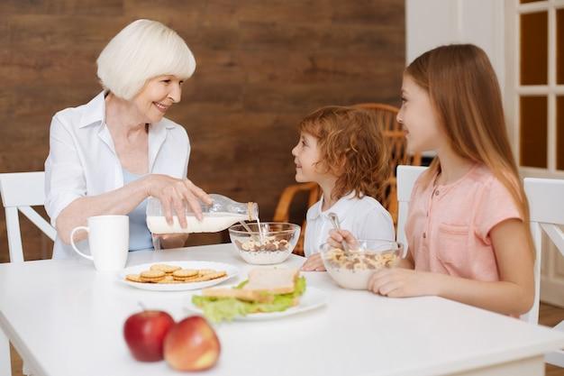 Actieve, heldere positieve familiebijeenkomst aan de tafel om te ontbijten terwijl oma verse melk in hun kommen schenkt