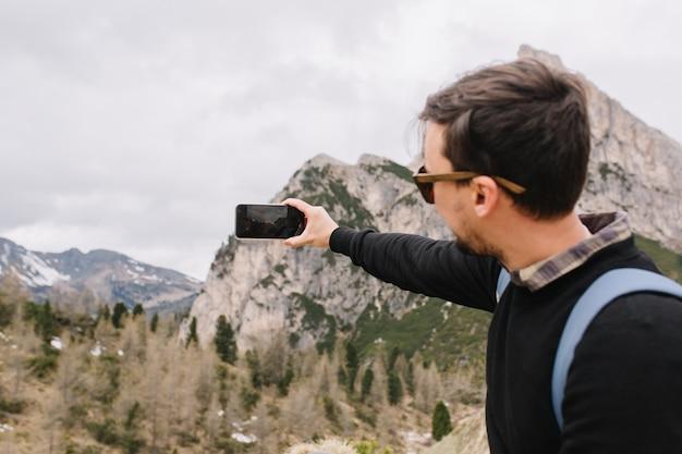 Actieve jonge man met donkerbruin haar, gekleed in een shirt onder een zwarte trui, reizen in de bergen en opgenomen video op smartphone