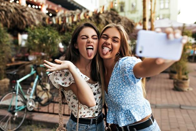 Actieve jonge meisjes in stijlvolle blouses trekken grappige gezichten, tonen tongen en nemen selfie
