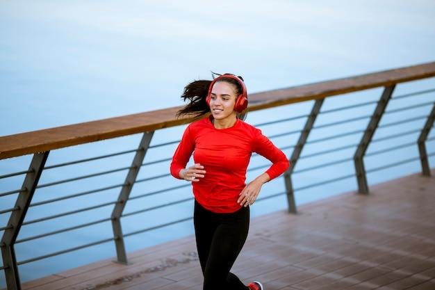 Actieve jonge mooie vrouw die op de promenade langs de rivier loopt