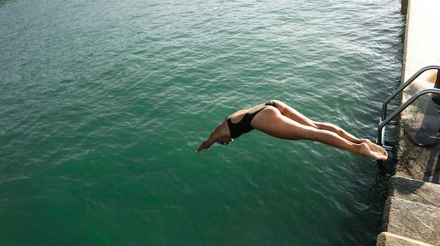 Actieve jonge vrouw die in het water springt