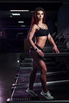 Actieve jonge vrouw en man die op tredmolen in gymnastiek lopen