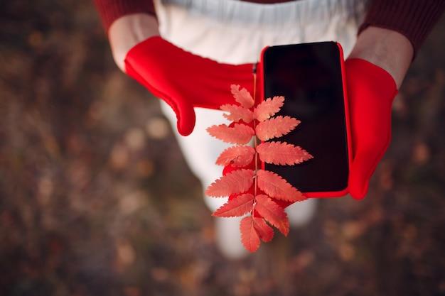 Actieve jonge vrouw in rode handschoenen en gezichtsmasker in het herfstpark met mobiele telefoon.