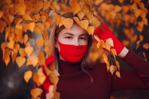 Actieve jonge vrouw in rode handschoenen en gezichtsmasker in het herfstpark.