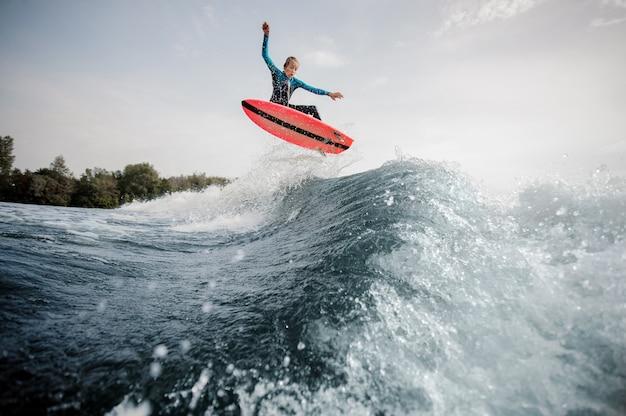Actieve jongen gekleed in zwarte en blauwe zwembroek surfen springen op oranje bord