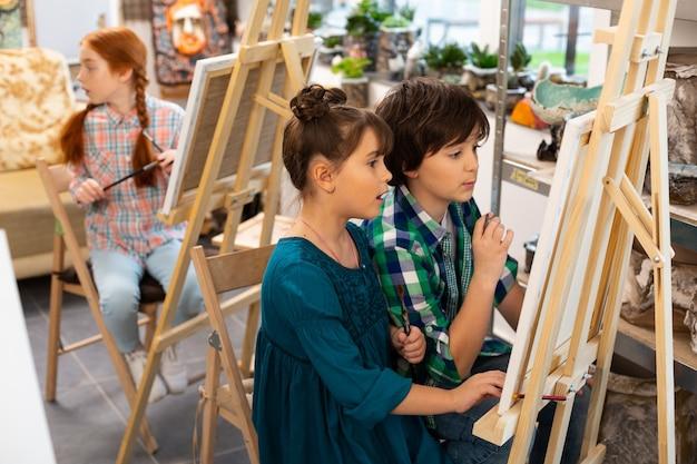 Actieve kinderen voelen zich opgewonden tijdens het tekenen op de kunstacademie