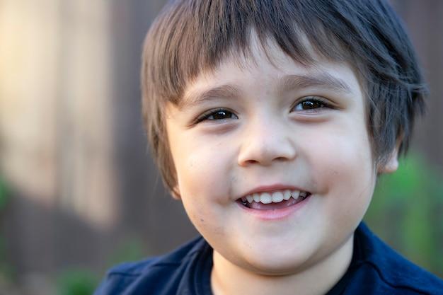 Actieve kleine jongen met vuile gezicht spelen buiten in de zomer
