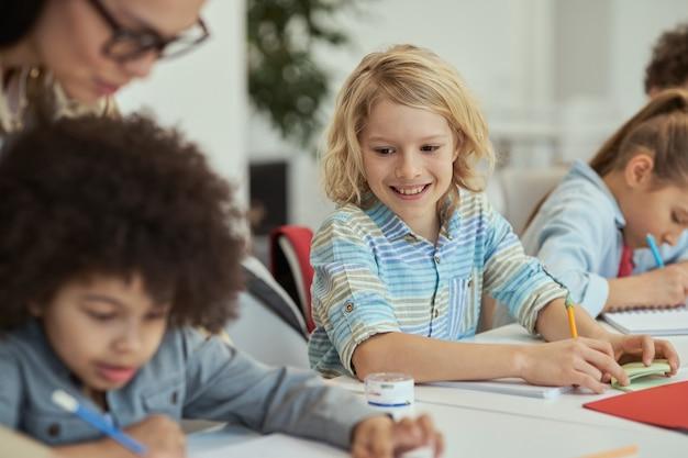 Actieve kleine schooljongen die lacht en naar zijn klasgenoot kijkt terwijl hij aan tafel zit