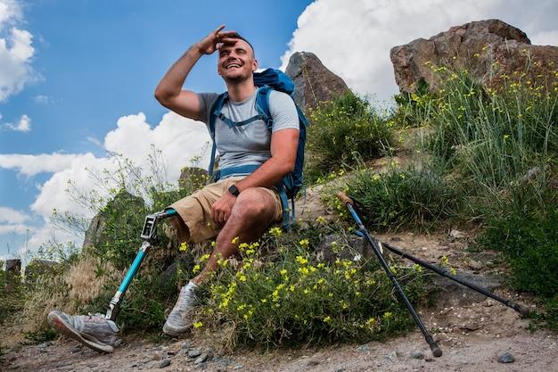 Actieve lachende jongeman met lichamelijke aandoeningen die geniet van natuurlijke uitzichten terwijl hij in het weekend uitrust