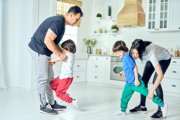 Actieve latijnse ouders van middelbare leeftijd die twee kleine jongens 's ochtends oefeningen laten doen. gezonde levensstijl. spaanse familie die thuis aan het trainen is
