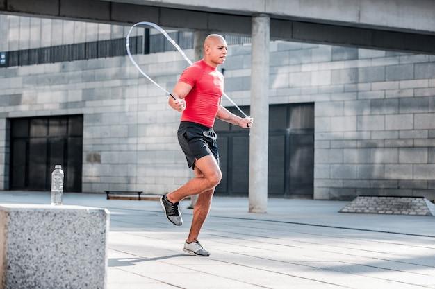 Actieve levensstijl. hardwerkende atletische man springen op een springtouw tijdens een training