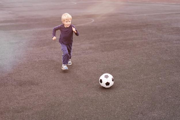 Actieve levensstijl in een moderne stad, kleine jongen die met een voetbal in het stadion speelt