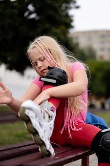 Actieve levensstijl in een moderne stad - meisje zet op rolschaatsen in het stadion