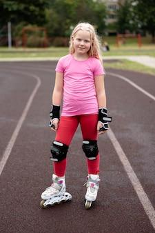 Actieve levensstijl in een moderne stad - stijlvol meisje rolschaatsen in een stadion