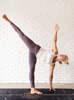 Actieve levensstijl. jonge aantrekkelijke vrouw die sportkleding draagt die thuis yoga beoefent. binnen volledige lengte, witte bakstenen muurachtergrond