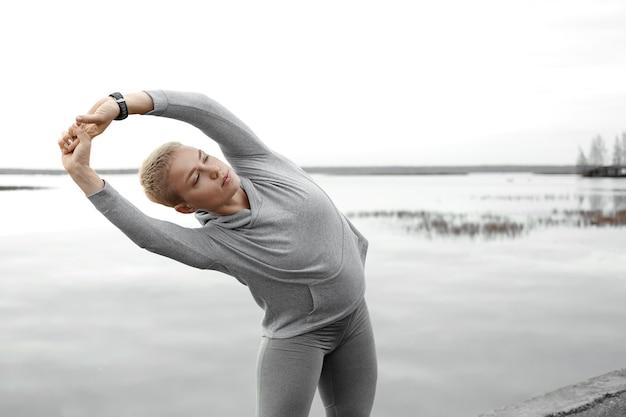 Actieve levensstijl, yoga, fitness en sportconcept. buitenaanzicht van sterke, flexibele jonge blanke vrouwelijke atleet die armen strekt, naar één kant buigt, lichaam opwarmt voordat de ochtend langs de rivieroever loopt